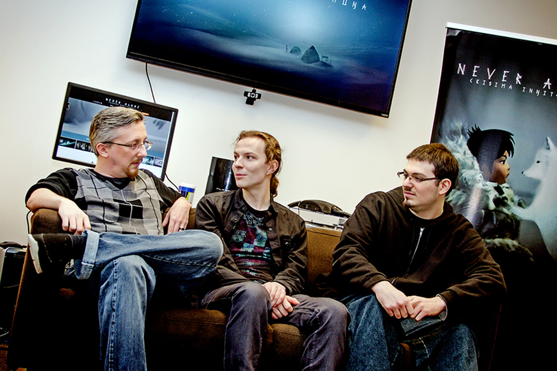 DigiPen alumni Matt Swanson, Alexei Gill, and Vincent Leone sitting on a couch in the E-Line Media office