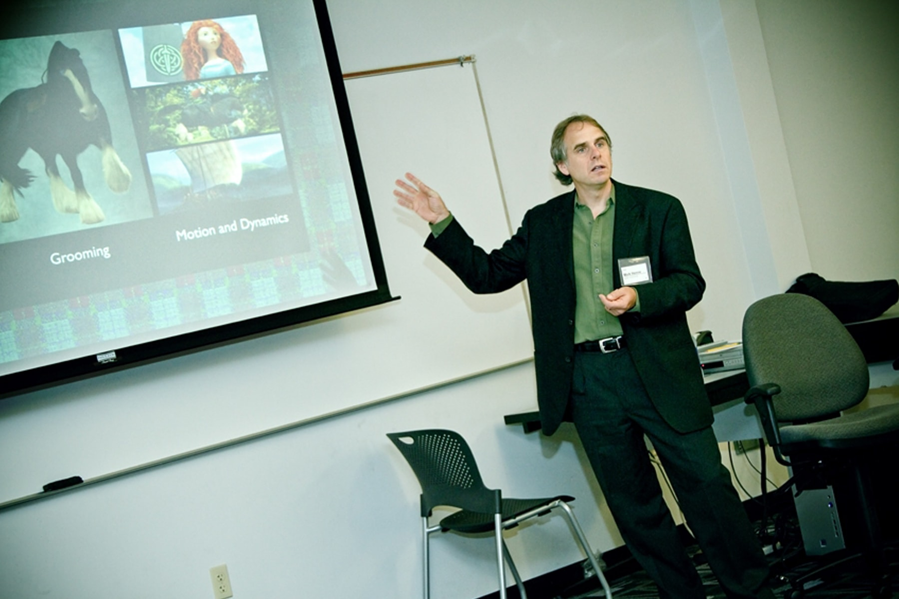 Mark Henne gestures toward a screen showing animated characters Princess Merida and her horse
