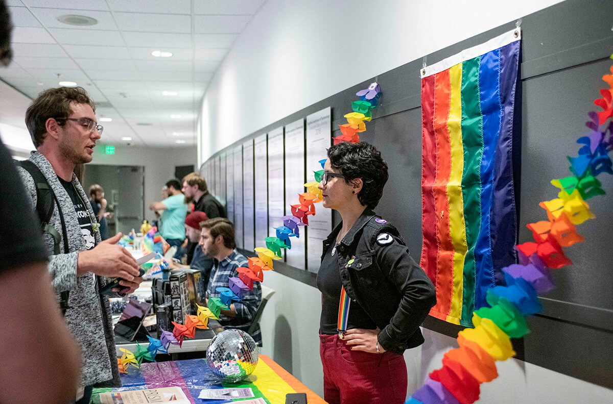 Students converse at a club info event; PRISM club representative stands at a table draped with rainbow-colored tablecloth and accordion streamers.