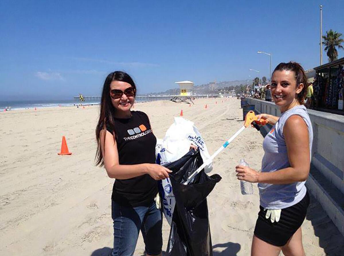 DigiPen graduate Romina Barrett volunteers with a fellow employee at The Control Group by collecting beach trash.