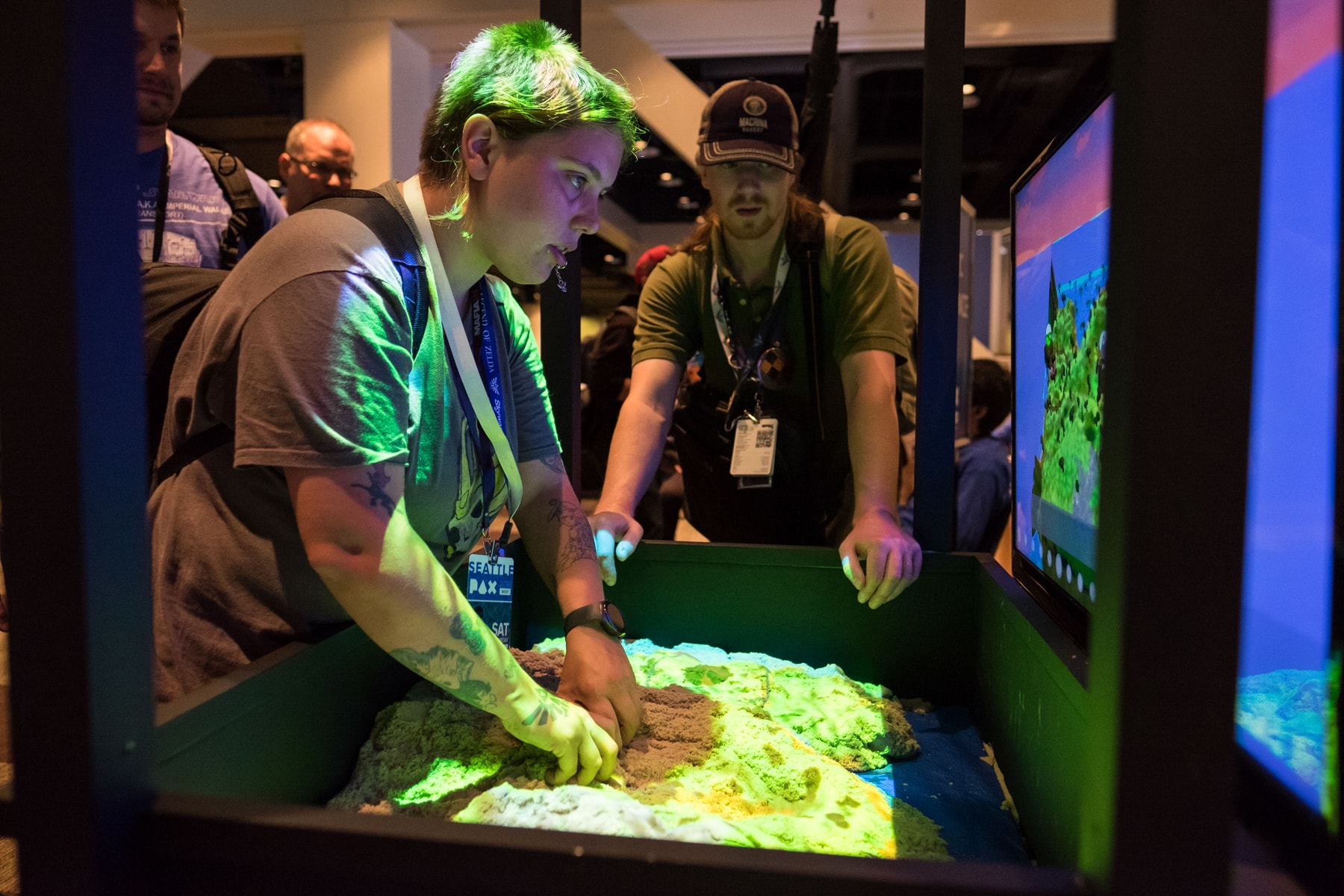 A PAX West attendee sculpting terrain by moving kinetic sand