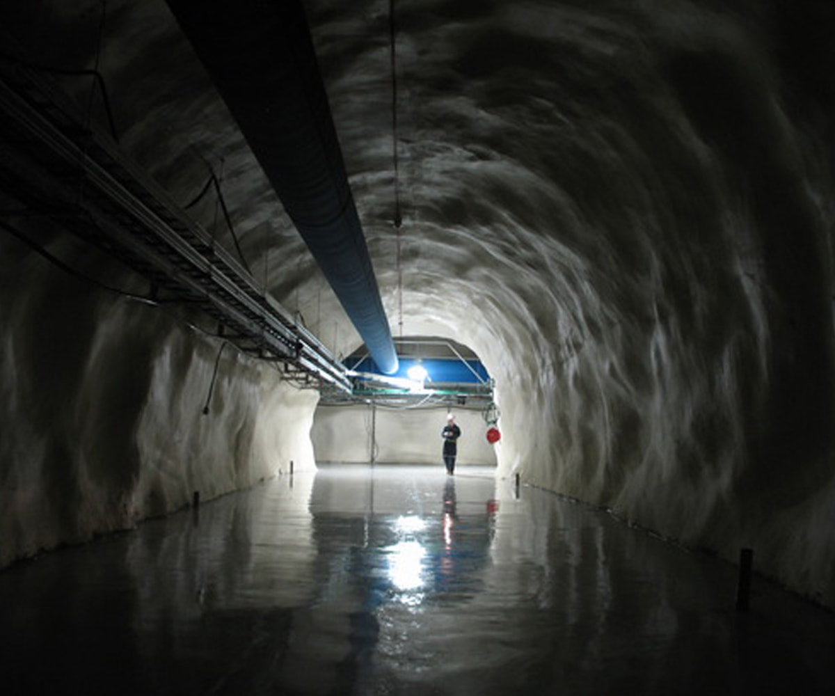 A worker standing in a dark, wet tunnel at SNOLAB
