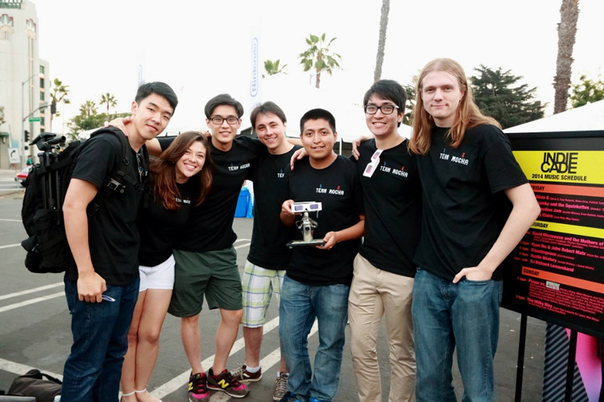 Seven members of DigiPen student game Team Mocha hold their award outside IndieCade