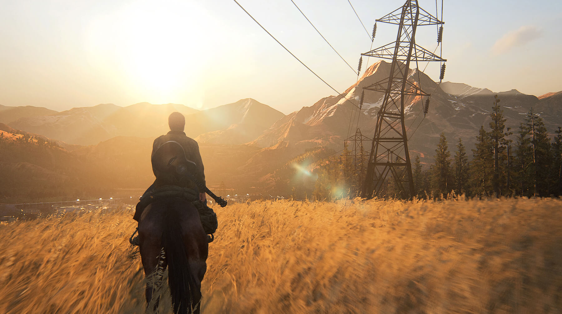 Ellie rides on horseback over a golden field with mountains in the background