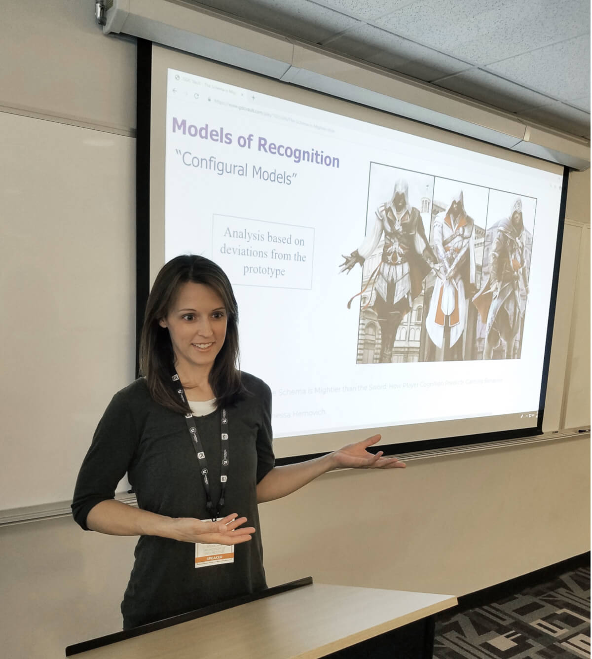 Professor Vanessa Hemovich lectures while gesturing at a slide showing characters from the game Assassin's Creed.