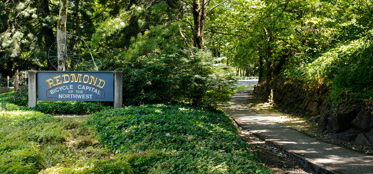 "Picture of a sign reading ""Redmond Bicycle Capital of the Northwest"" next to a wooded trail"