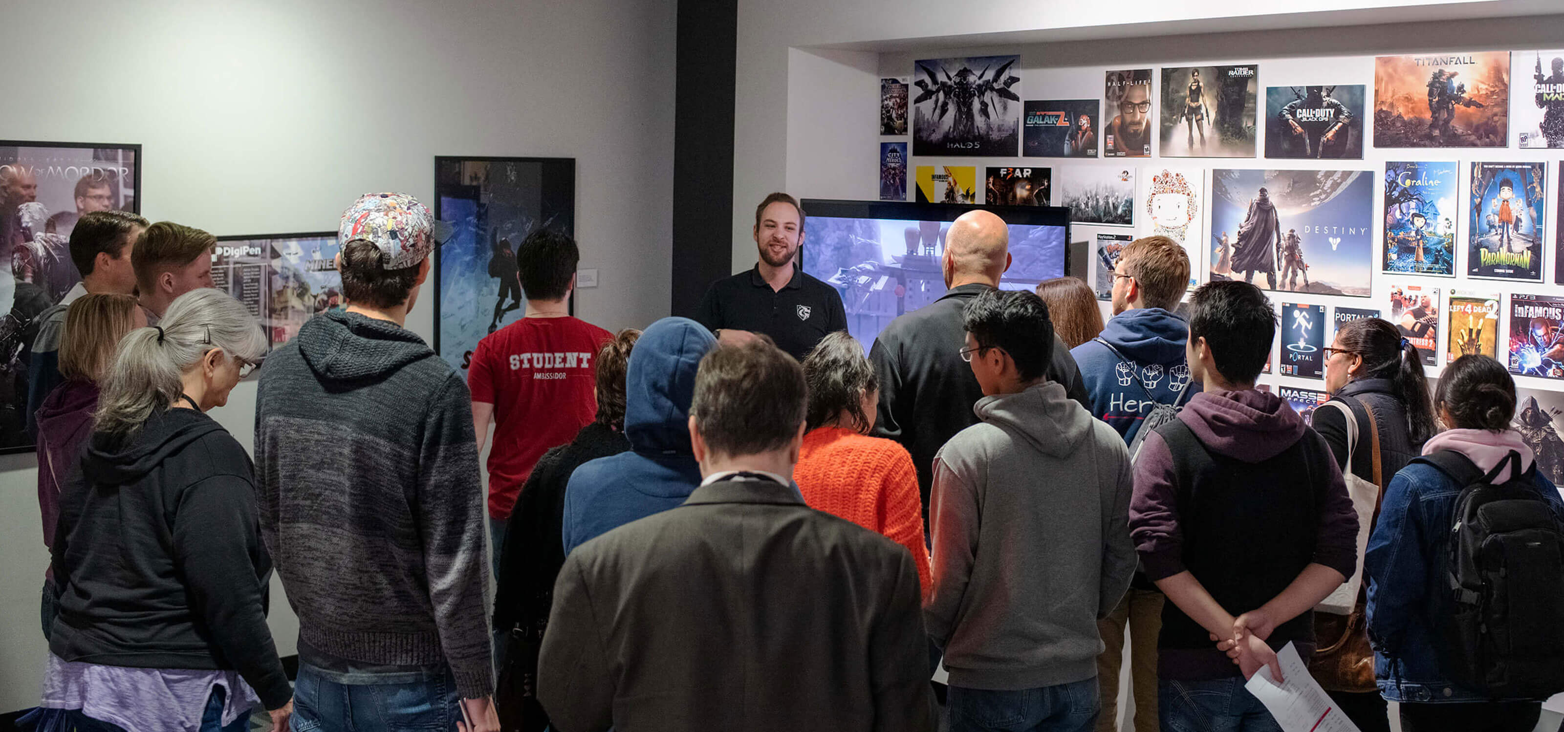 A group of people seen from behind as a man in a black polo shirt addresses them in a hallway strewn with video game posters.