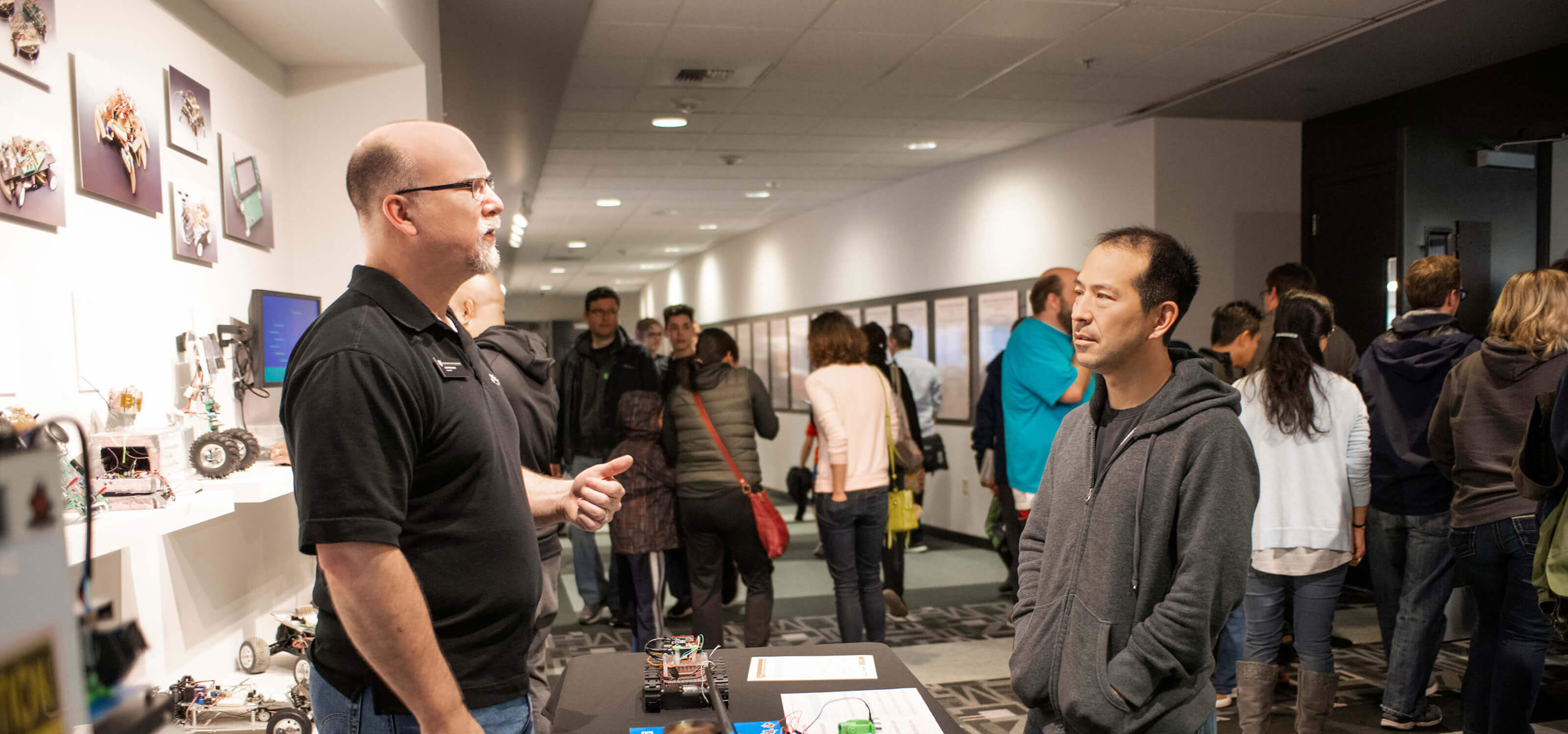 A DigiPen staff member speaks with a prospective student at a Preview Day event