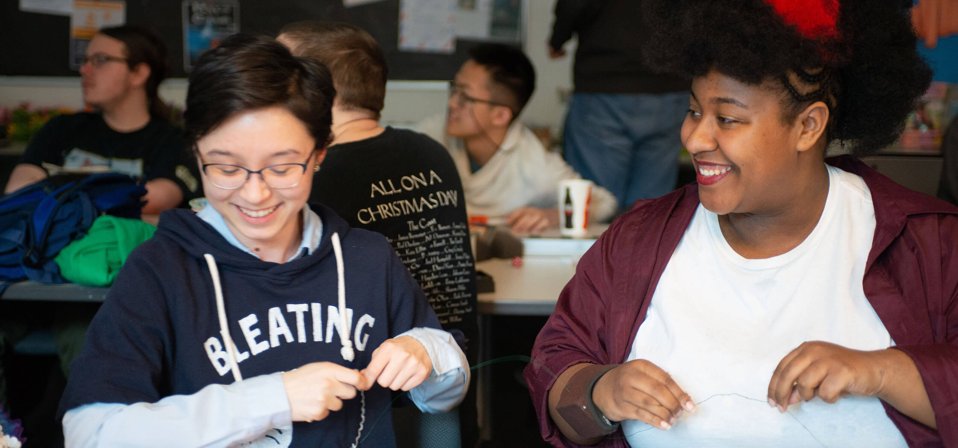 Two DigiPen students smile as they work on crafts together