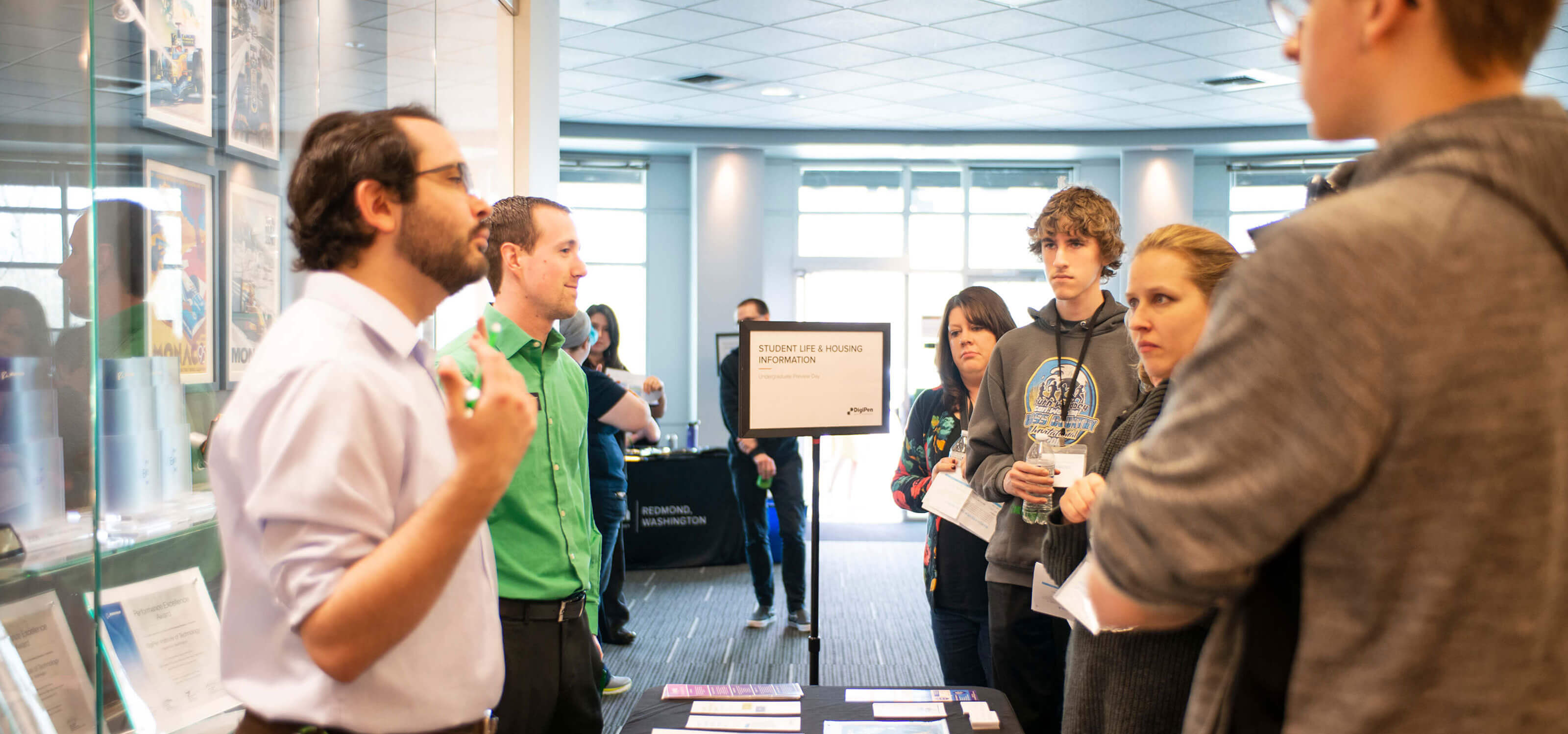 A DigiPen staff member speaks with prospective students and parents at a Preview Day event