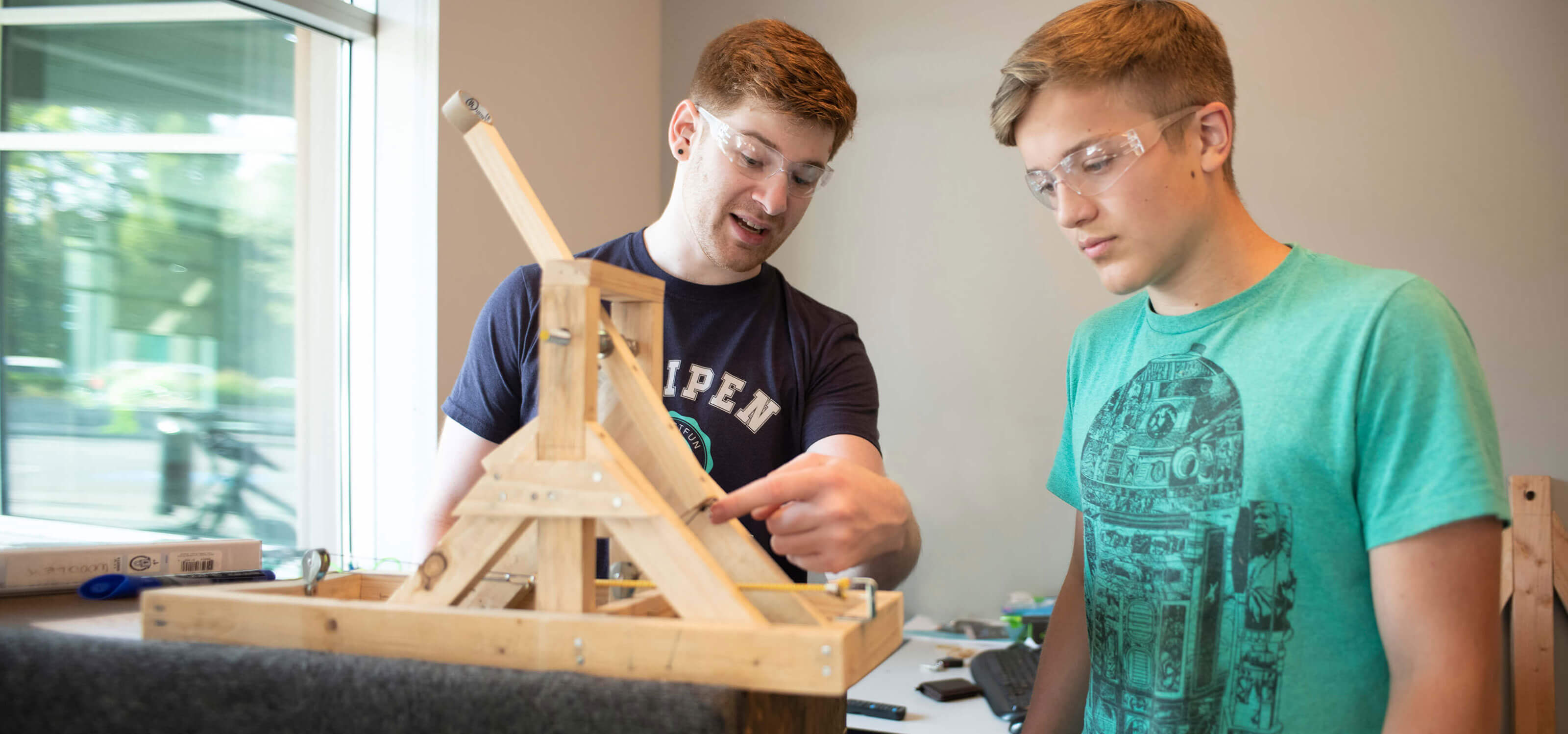 A DigiPen ProjectFUN instructor gestures at a wooden contraption as a student looks on